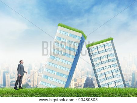 Businessman and falling buildings