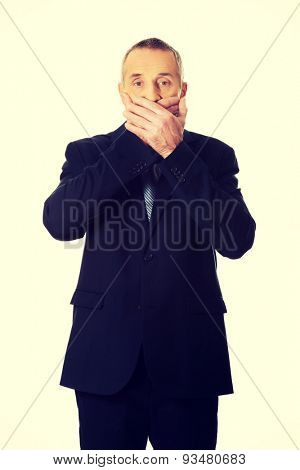 Shocked mature businessman covering mouth.