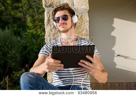casual man holding a tablet with headphones, outdoor