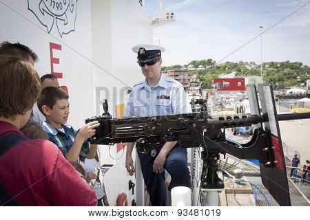 STATEN ISLAND, NY - MAY 24 2015: An unidentified boy looks through the scope of a .50 caliber machine-gun aboard the USCGC Spencer (WMEC 905) at Sullivans Pier during a public tour at Fleet Week 2015.