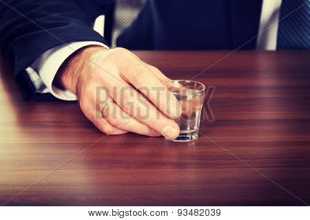 Businessman's hand with a glass of alcohol.