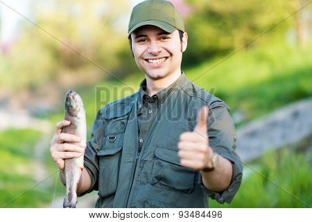 Portrait of an happy fisherman holding a fish