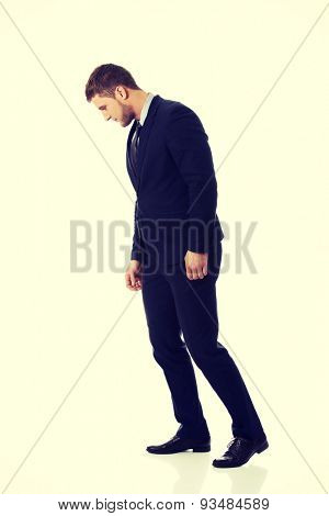 Handsome businessman looking down on the floor.