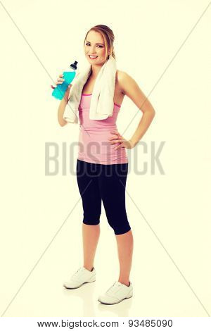 Attractive woman in fitness clothes drinking isotonic drink.