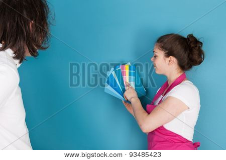 Woman with color samples against blue wall