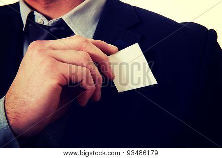 Young businessman taking his personal card from pocket.