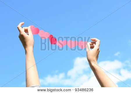 Female hands with chain of paper hearts on blue sky background