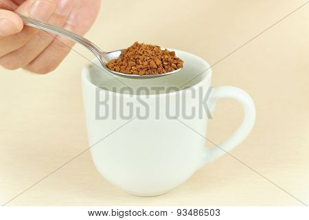 Hand holding a spoon with instant coffee over cup of water