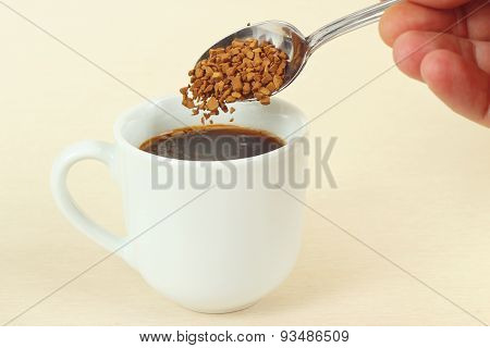 Hand pours granulated coffee from a spoon in coffee cup
