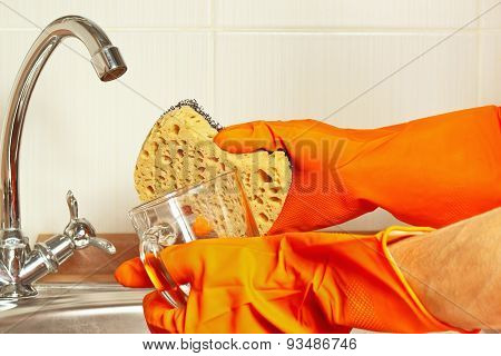 Hands in rubber gloves with sponge and dirty cup over the sink in kitchen