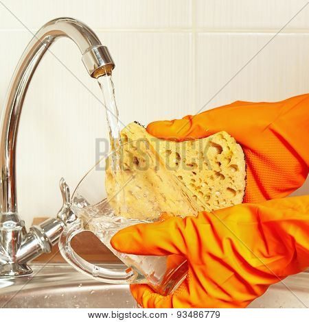 Hands in gloves wash the dirty glass under running water in kitchen