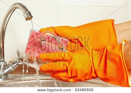Hands in rubber gloves wash glass under running water