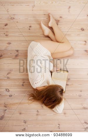Casual female student lying on floor with book reading. Indoor.