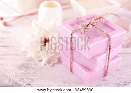 Stack of tied spa soap on wooden table, closeup