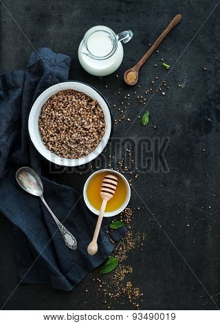 Rustic healthy breakfast set. Cooked buckwheat groats with milk and honey on dark grunge backdrop
