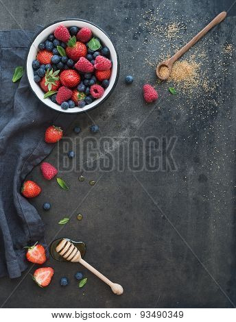 Berry frame with copy space on right. Strawberries, raspberries, blueberries and mint leaves, dark g