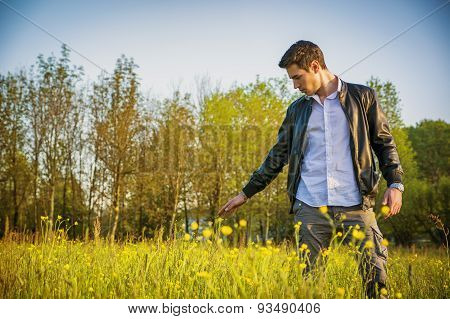 Handsome young man at countryside, in field or grassland