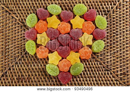 Gummy candies arranged in heart shape on wicker background