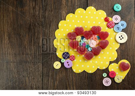 Gummy candies arranged in heart shape with buttons on table close up
