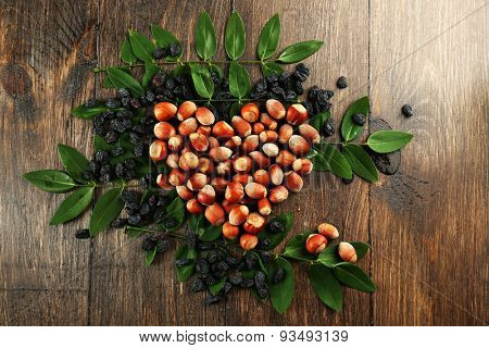 Hazelnuts with raisins arranged in heart shape on wooden background