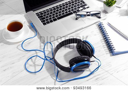 Workplace with headphones on table close up