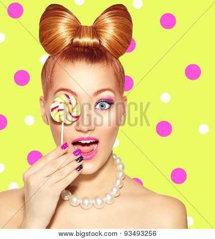 Beauty fashion model girl Eating colourful lollipop. Surprised Young funny woman with bow hairstyle, pink nail art and makeup over bright green with pink polka dots background