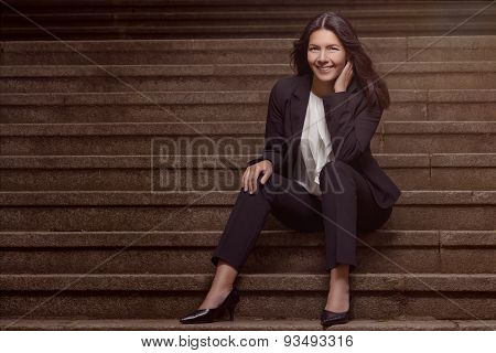 Smiling Stylish Woman Sitting On Steps