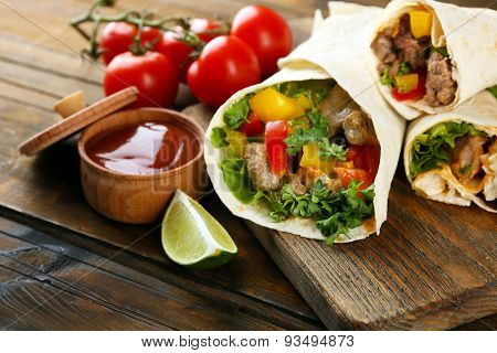 Homemade tasty burritos with vegetables, potato chips on cutting board, on wooden background