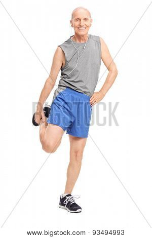 Full length portrait of a senior in sportswear stretching his leg and listening music on headphones isolated on white background