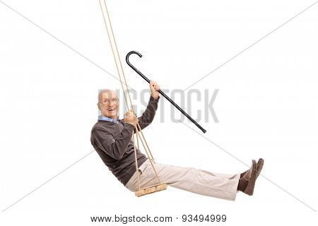 Studio shot of a joyful senior swinging on a swing and holding a cane isolated on white background