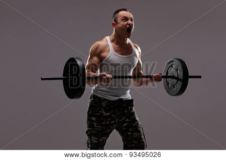 Determined young athlete exercising with a barbell and shouting on gray background
