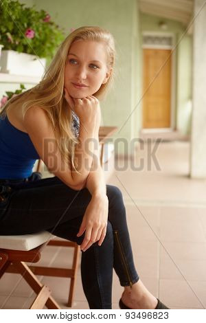 Daydreaming young woman sitting on balcony, smiling, looking away.