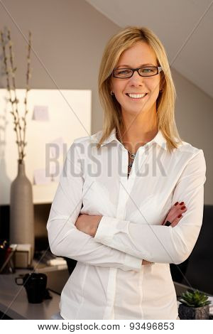 Portrait of confident businesswoman smiling arms crossed, looking at camera.