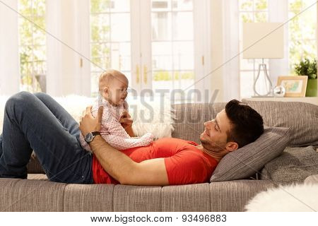 Young father holding little daughter on his belly as lying on sofa, playing. Side view.