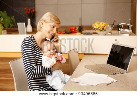 Young mother working from home, holding baby on lap.