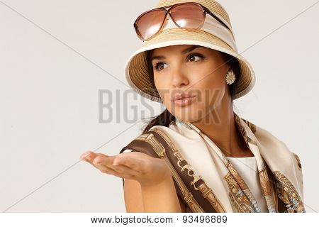 Attractive young woman blowing a kiss at summertime, wearing hat, looking away.