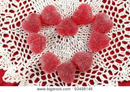 Gummy candies arranged in heart shape on fabric background