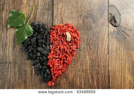 Goji berries and raisins arranged in heart shape on wooden background