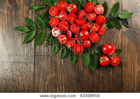 Cherry tomatoes arranged in heart shape with green leaves on wooden background