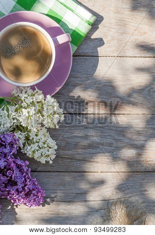 Coffee cup and colorful lilac flowers on garden table. Top view with copy space