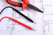 picture of pliers  - Cables of multimeter and metal pliers lying on construction drawings of house electrical drawings and work tools for engineer jobs - JPG
