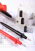 foto of electrical engineering  - Cables of multimeter and electric fuse lying on construction drawings of house electrical drawings and tools for engineer jobs - JPG