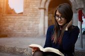 Постер, плакат: Charming teenager spectacled sitting outdoors with open book and absorbs knowledge