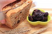 foto of fresh slice bread  - Slicing fresh baked wholemeal bread heap of dried plums and ears of wheat lying on cutting board concept for healthy eating - JPG