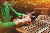 stock photo of internet-cafe  - Side view male freelancer sitting on the terrace  while having a break man - JPG