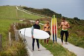 foto of board-walk  - Group of three surfers walking down nature road relaxing after surf session surfers walking towards the beach wearing wetsuits and boards summer holidays on surf camp with friends - JPG