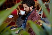 stock photo of coffee coffee plant  - Side view through plant leaves pensive man holding cup of tea or coffee next to his mouth while sitting on the terrace of beautiful coffee shop - JPG