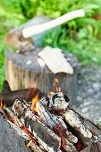 picture of brazier  - firewood burning in rusty brazier close up with ax in stump on background - JPG