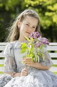 image of polite girl  - Girl portrait holding flowers near her face - JPG