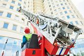 image of firemen  - fireman climbing a ladder with water hose for extinguish fire - JPG
